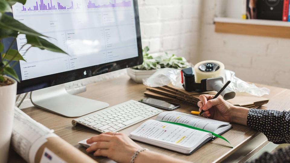 Concurso Vale do Sol - RS: pessoa usando computador e escrevendo num caderno