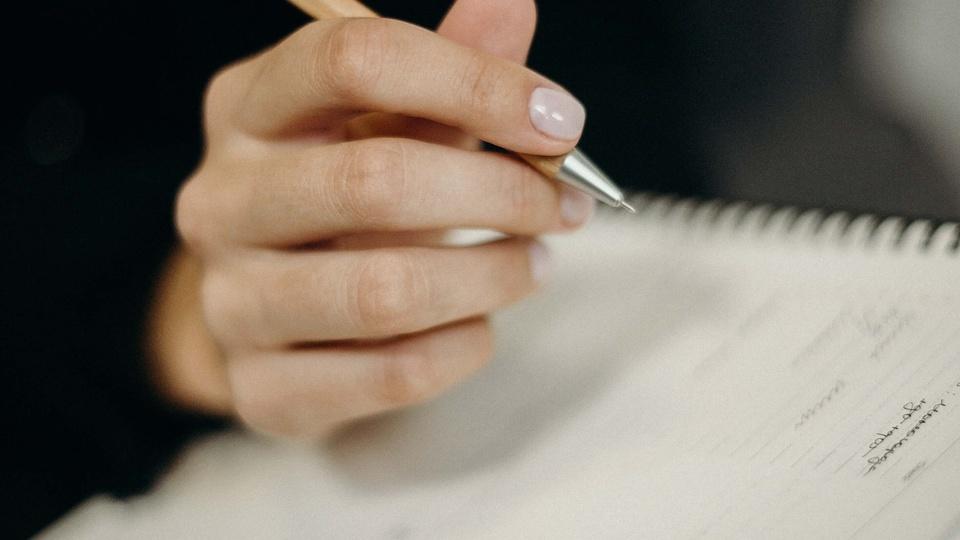 Concurso Prefeitura de Vinhedo - SP: a foto mostra mulher escrevendo em um caderno