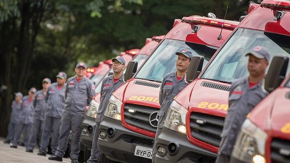Concurso Bombeiros AL: bombeiros e veículos do corpo de bombeiros enfileirados.