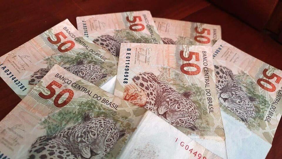 Benefícios sociais do governo: notas de cinquenta reais espalhadas em superfície plana