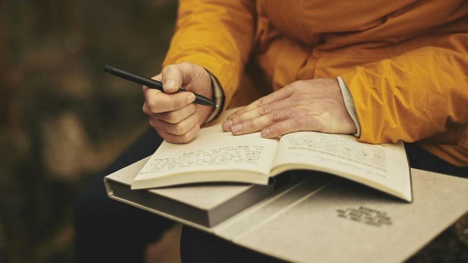 Processo seletivo CEMMIL Saneamento Ambiental – SP: pessoa estudando com um caderno aberto e segurando uma caneta