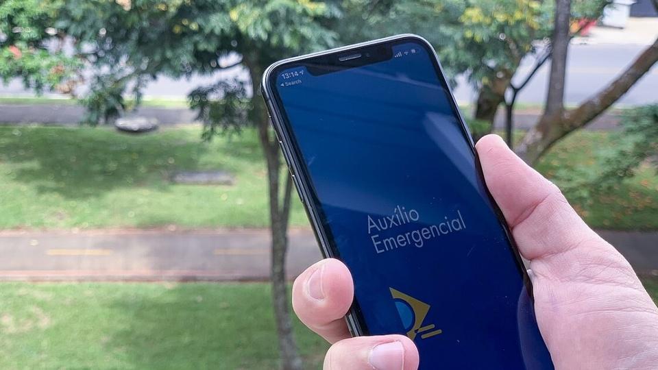 Consulta de auxílio emergencial pelo aplicativo: enquadramento em mão segurando celular. Na tela do aparelho, é possível ver a página inicial do auxílio emergencial