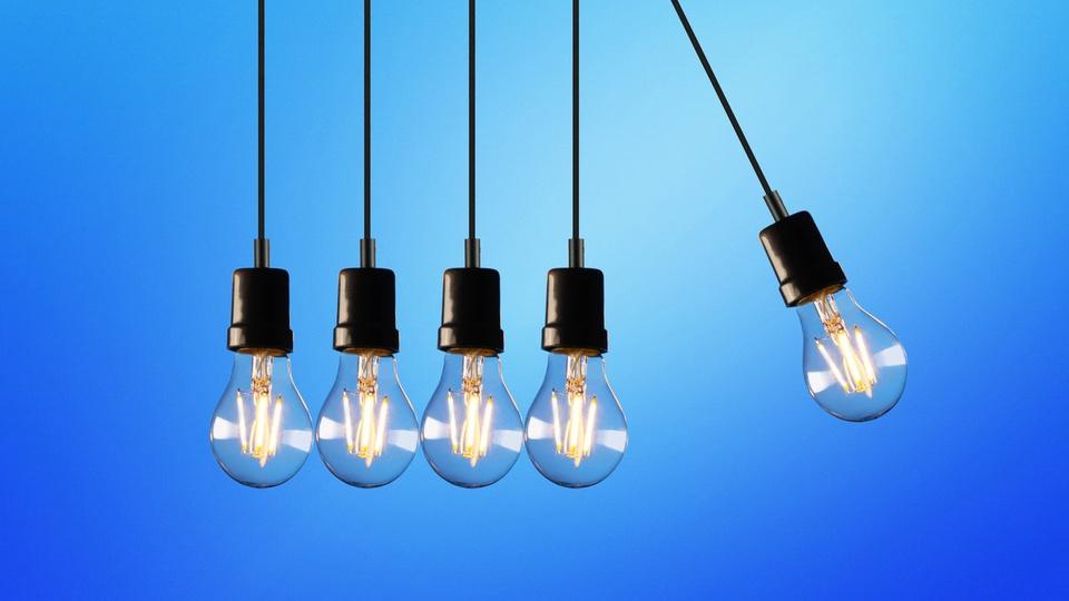 Conta de luz: quatro lâmpadas penduradas pelo fio de energia e uma balançando como pêndulo