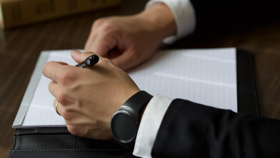contratações por concurso público: a imagem mostra pessoa vestida de terno escrevendo algo em papel