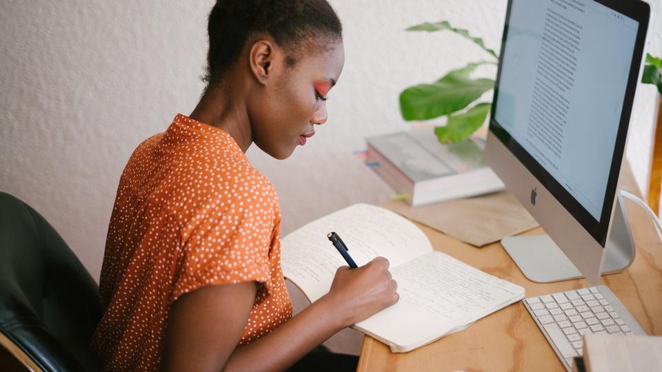 Convocação em concurso, mulher fazendo anotação em um papel e de frente a um computador