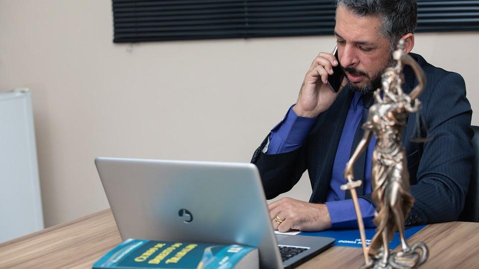 Processo seletivo EBSERH: homem em escritório, falando em celular e usando o notebook