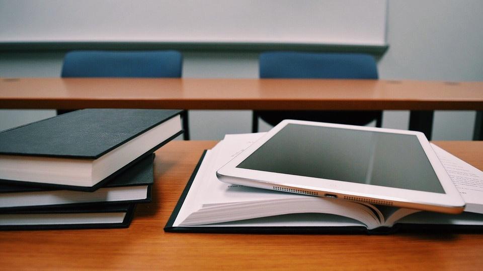 Curso online ou presencial para concurso: tablet sobre livro aberto ao lado de livros empilhados em cima de uma mesa dentro de sala de aula.