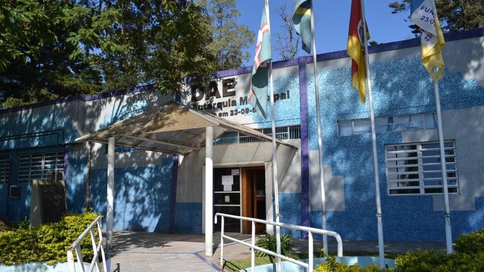 Processo seletivo DAE de Santana do Livramento: a imagem a fachada do Departamento de Água e Esgoto de Santana do Livramento com três bandeiras na frente do prédio