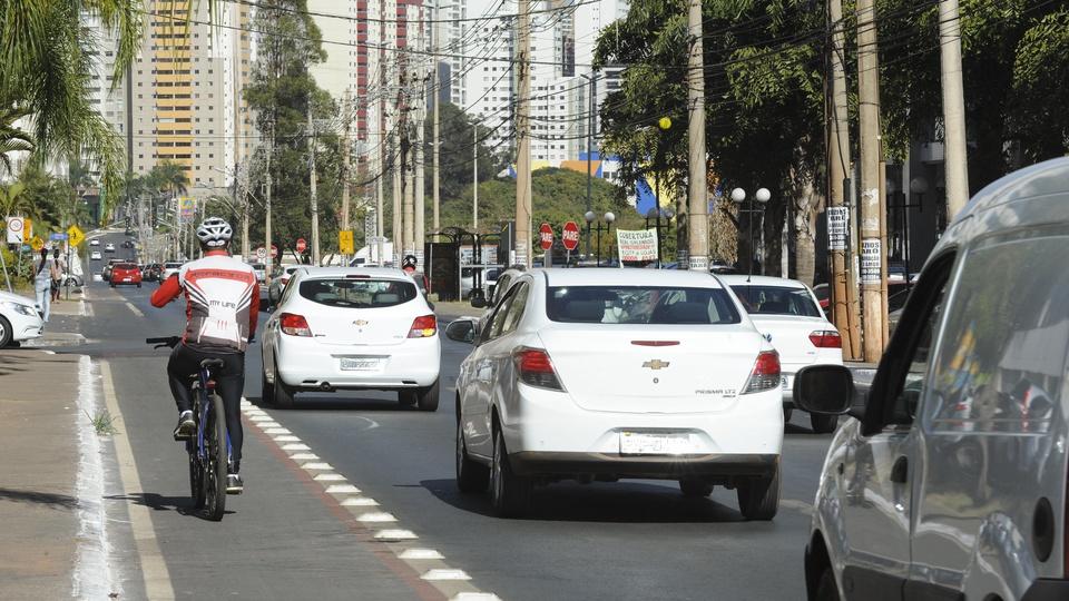 Deputado quer fim da obrigatoriedade de autoescola para tirar CNH, rua com carros e ciclista