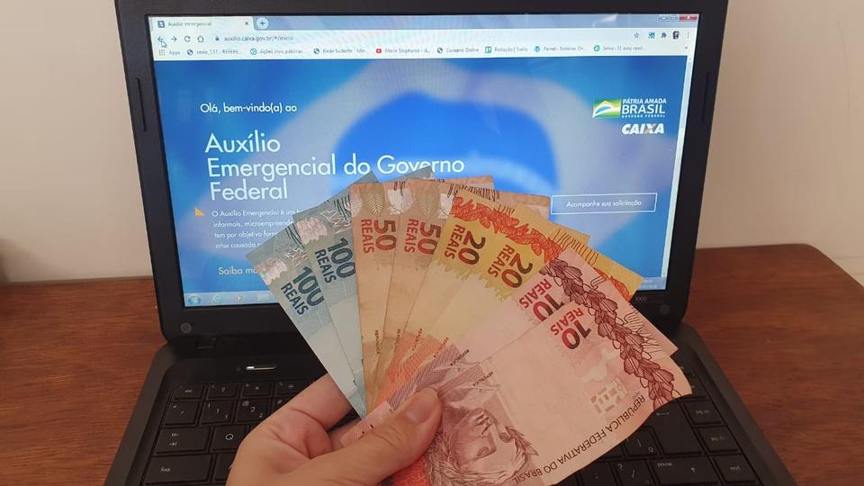 auxílio emergencial: mão segurando leque de dinheiro com notas de 100, 50, 20 e 10 reais em frente a computador aberto no site do auxílio emergencial