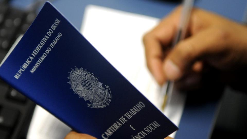 """Desalento: 5,4 milhões de brasileiros """"desistiram"""" de buscar emprego, mão escrevendo em carteira de trabalho com caneta"""