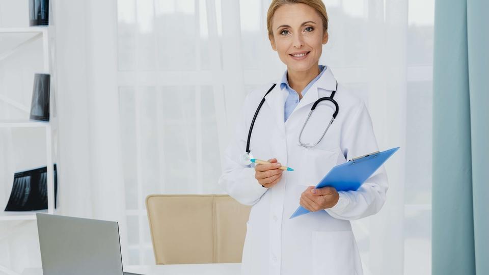 Mais Médicos: médica segurando uma prancheta azul. Ela está usando um jaleco e no pescoço está um estetoscópio.