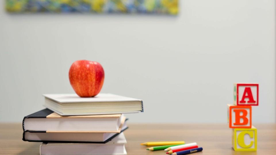 Prefeitura de Paudalho: a foto mostra uma classe ou mesa onde há alguns lápis, livros e uma maçã em cima da pilha de livros
