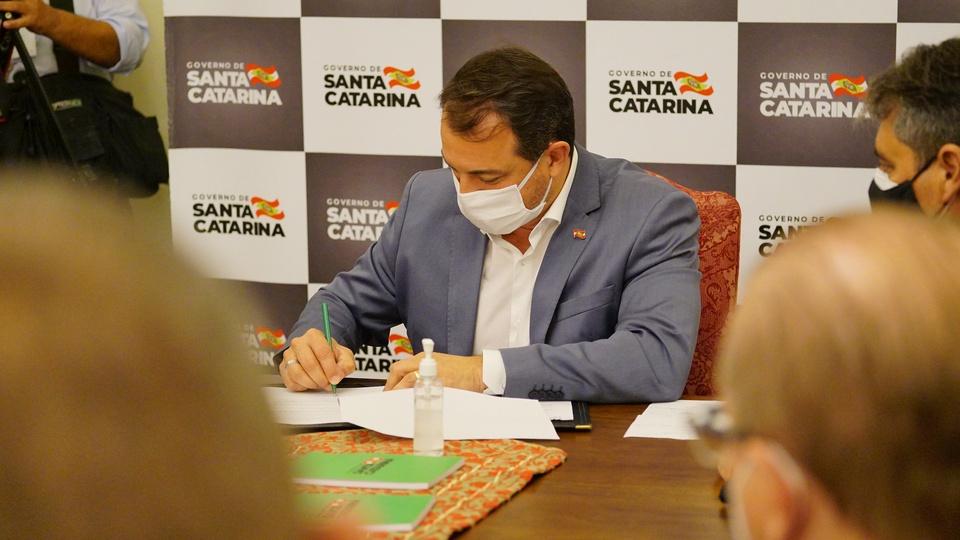 Auxílio emergencial para empreendedores: governador de Santa Catarina, Carlos Moisés, sentado e assinando documento