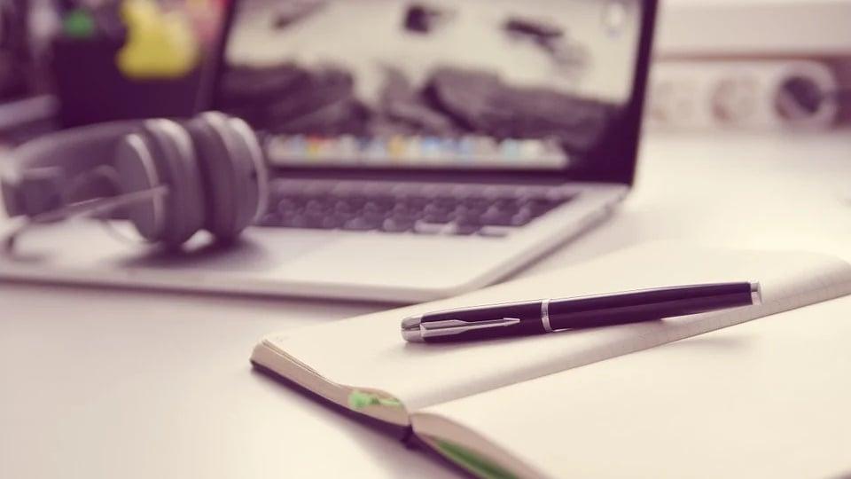 ESPMT: a foto mostra numa mesa caderno, caneta, fone de ouvido e notebook