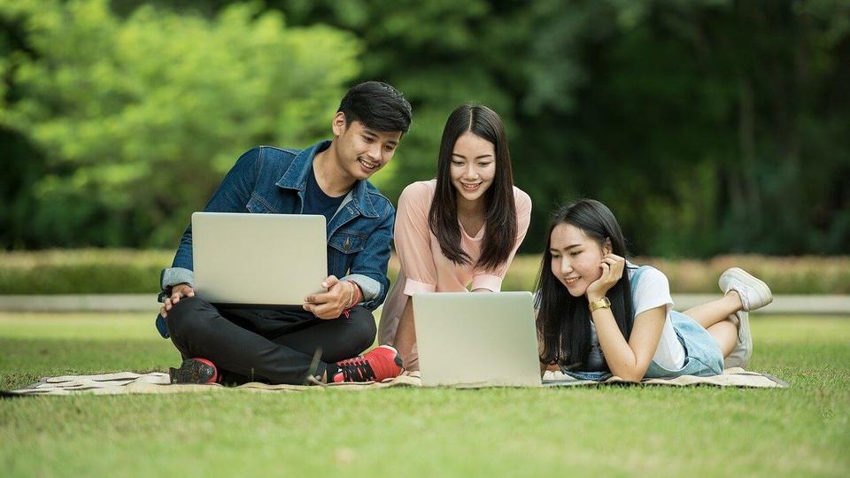 MSGÁS: a foto mostra três estudantes um homem e duas mulheres jovens sentados num gramado ao ar livre e portando notebooks