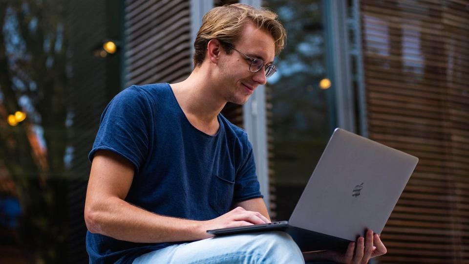 Estágio PGE PA: homem de óculos de grau, sentado e com notebook no colo; rapaz está usando o aparelho