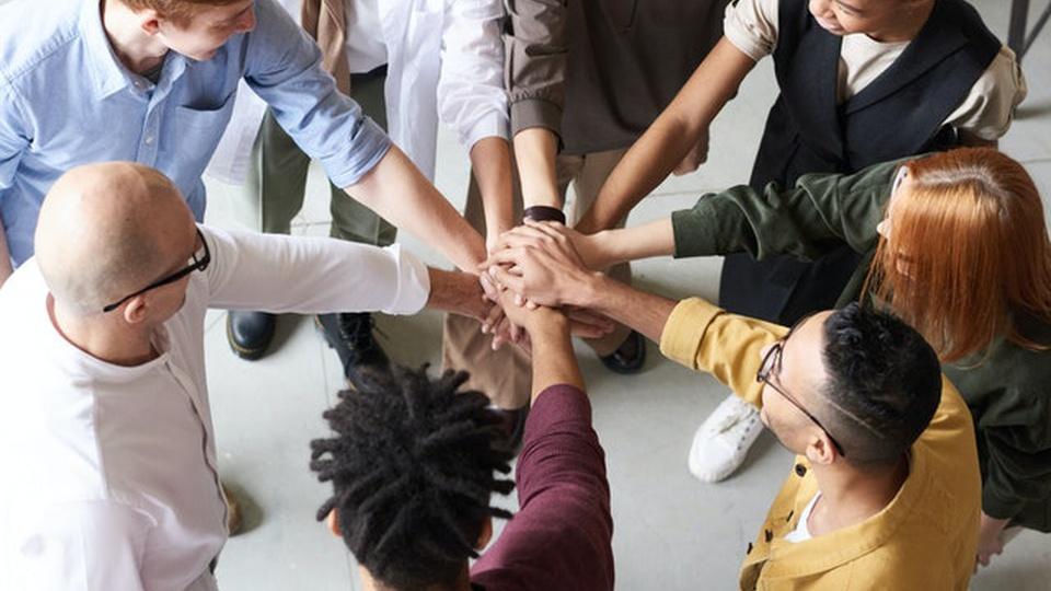 Prefeitura de Lajeado: pessoas jovens de pé, em círculo e com as mãos unidas