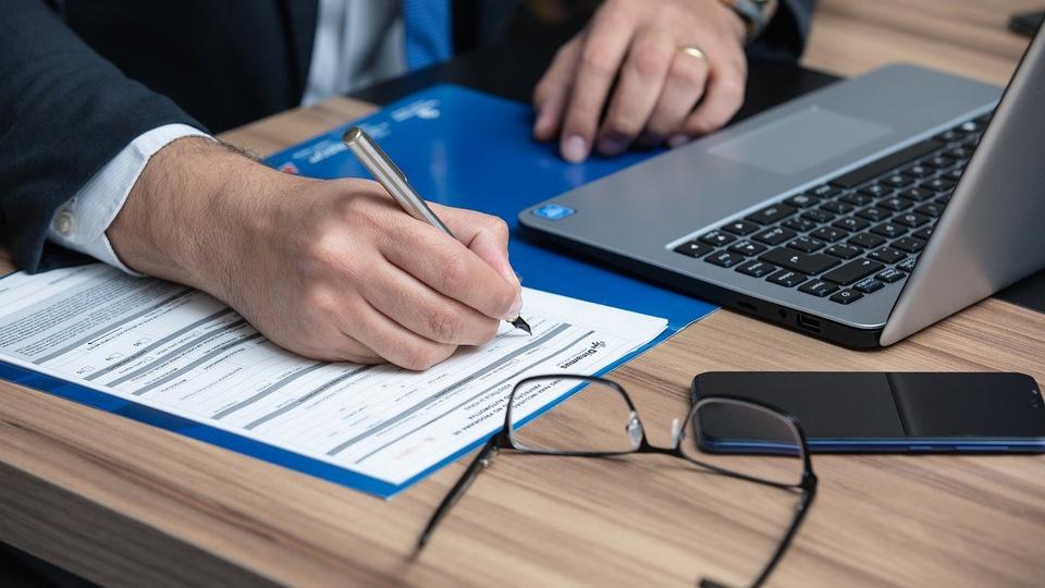 Processo seletivo Prefeitura de Perdões - MG: notebook, óculos de grau e folhas sob mesa; homem escreve em folha com caneta