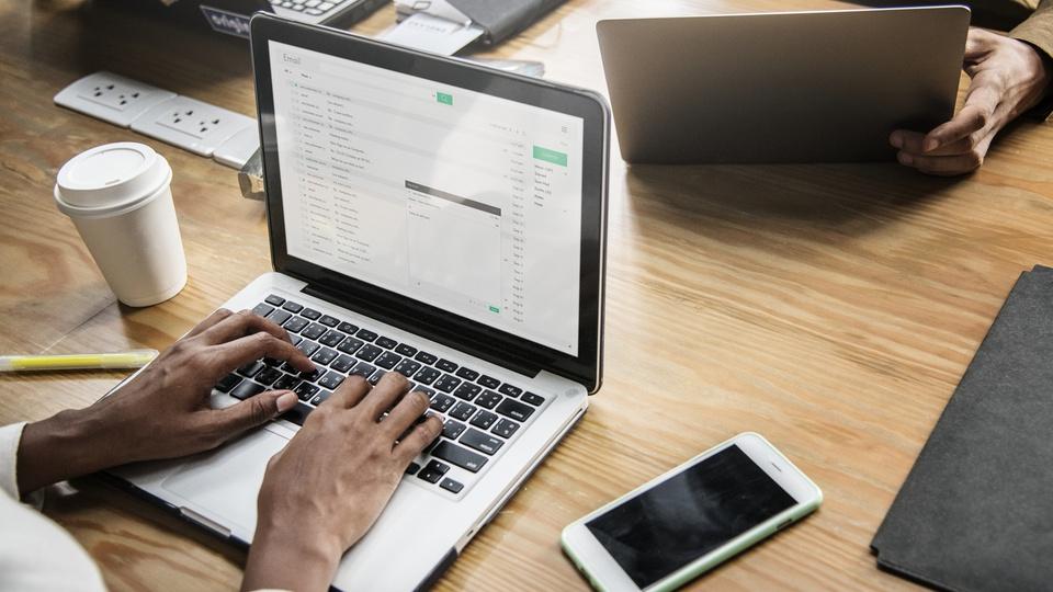 Estágio PRFN: dois notebooks, celular e copo de café em cima da mesa; homem digita em teclado de um notebook