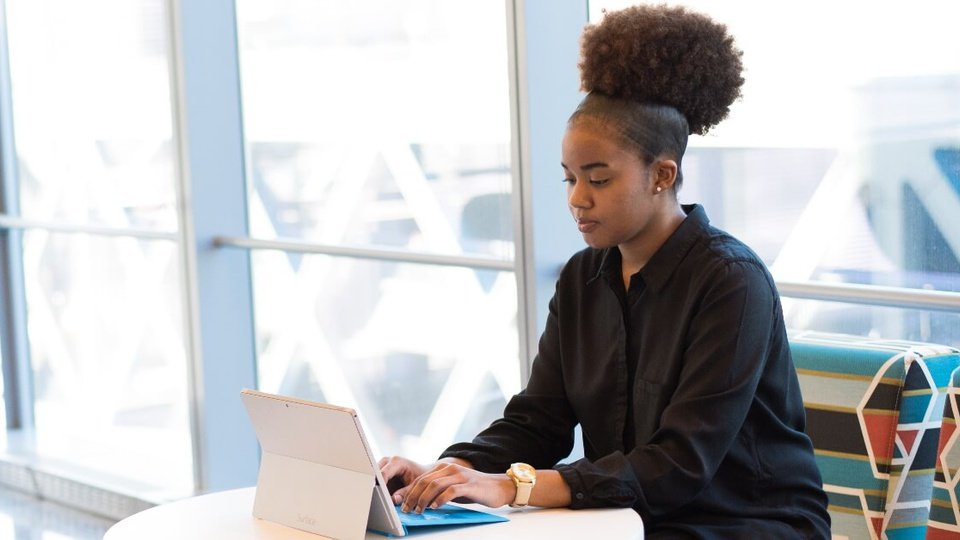 Processo seletivo de Estágio TRT GO: enquadramento médio em jovem negra digitando em notebook. Ela está sentada em uma cadeira