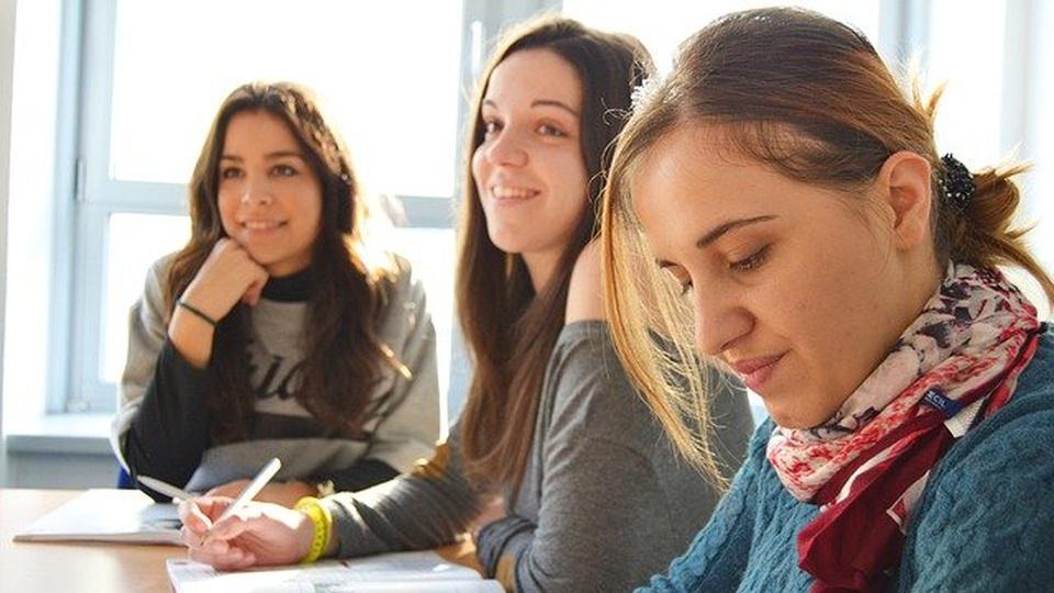 UNILAB: três jovens estudantes com livros e prestando atenção em alguém