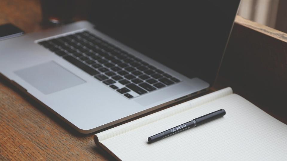 Estudantes de escolas públicas não têm computador: é possível ver, em uma superfície plana, um notebook ao lado de um caderno com folhas em branco