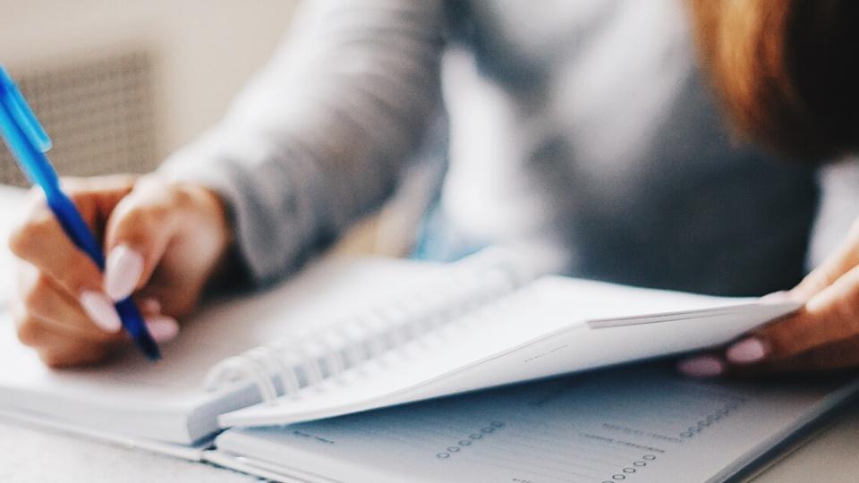 Estudo pós-edital de concurso: enquadramento em mãos escrevendo em caderno