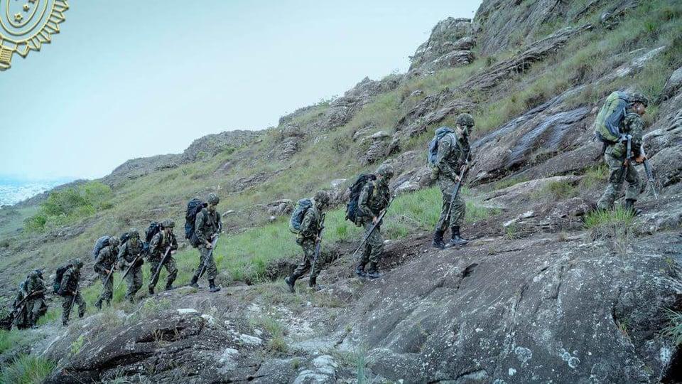 Exercito Brasileiro: a foto mostra militares do exército em treinamento numa região florestal íngreme, estão fardados com o uniforme padrão do exército brasileiro