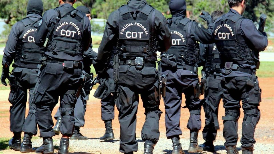 Polícia Federal: agentes da PF uniformizados de preto e armados de costas