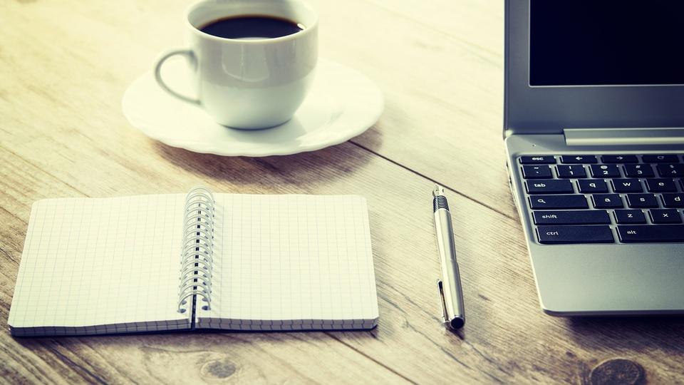 Êxito empreendedorismo: imagem mostra xícara de café sobre pires, cardeno aberto com caneta ao lado e computador em cima de mesa de madeira