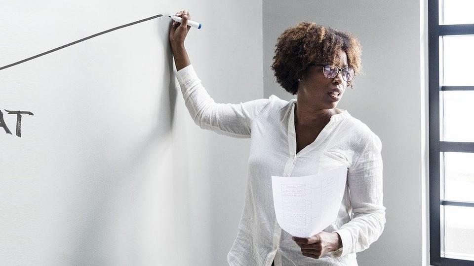 Processo seletivo FAESPE - GO (Fundação Antares): professora escrevendo no quadro branco com marcador