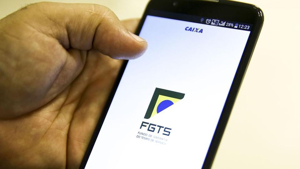 fgts emergencial 2021: a imagem mostra mão segurando celular aberto no app do fgts emergencial