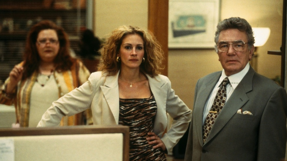 """Filmes para concurseiros: cena do filme """"erin Brockovich"""", em que a atriz principal e dois homens olham para frente"""