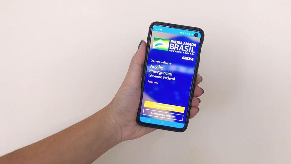 Desempregado pode receber o auxílio emergencial 2021: mão segurando celular. Na tela do aparelho, é possível ver a página do auxílio emergencial