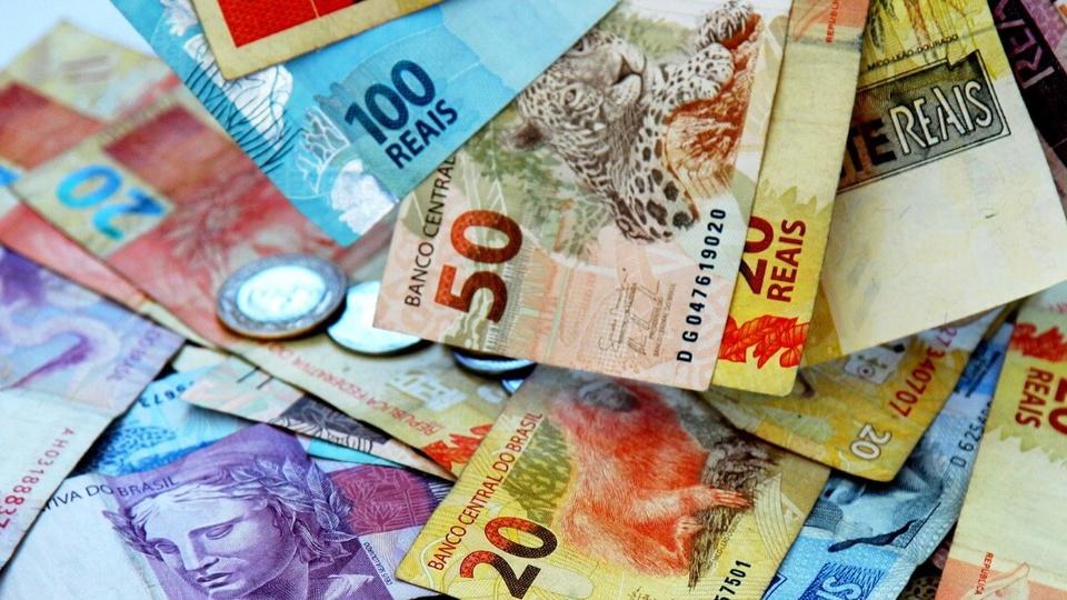 Fraudes no auxílio emergencial: enquadramento fechado em cédulas de dinheiro espalhadas em superfície plana