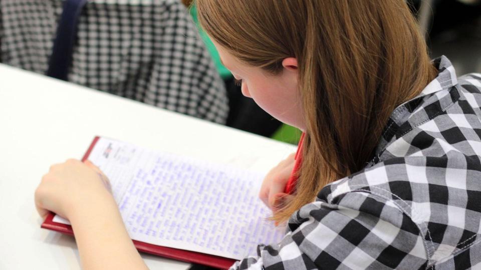 FUNCAMP - SP abre vagas: foco em mulher escrevendo em caderno