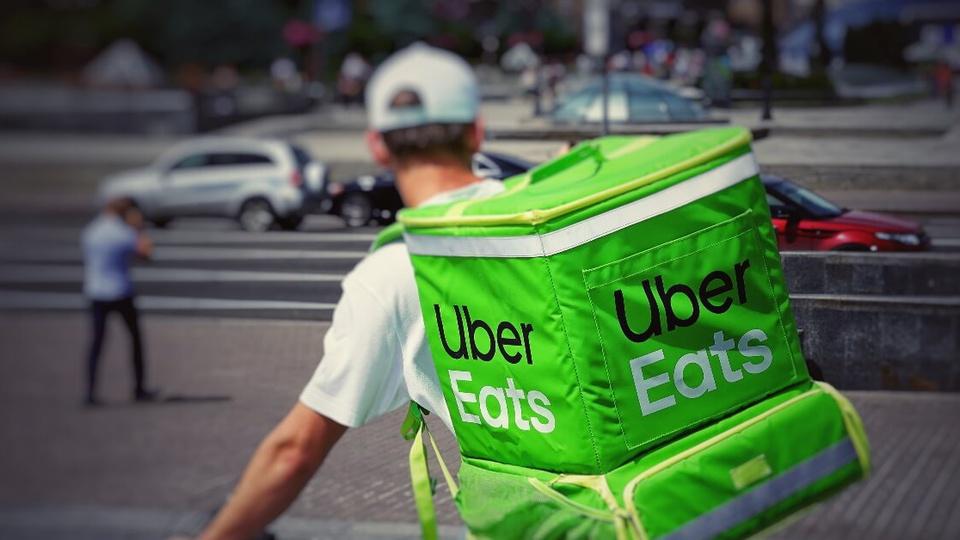 Gastos com aplicativos de comida: em destaque, entregador de delivery andando de bicicleta. Nas suas costas, é possível ver uma espécie de mochila típica para entrega de pedidos em aplicativos. Ela é toda verde, com a logomarca da UberEats bem no centro