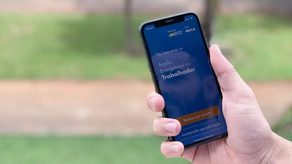 Golpe do auxílio emergencial: enquadramento fechado em mão segurando o celular. Na tela, é possível ver a página inicial do aplicativo da Caixa para pedir o auxílio emergencial
