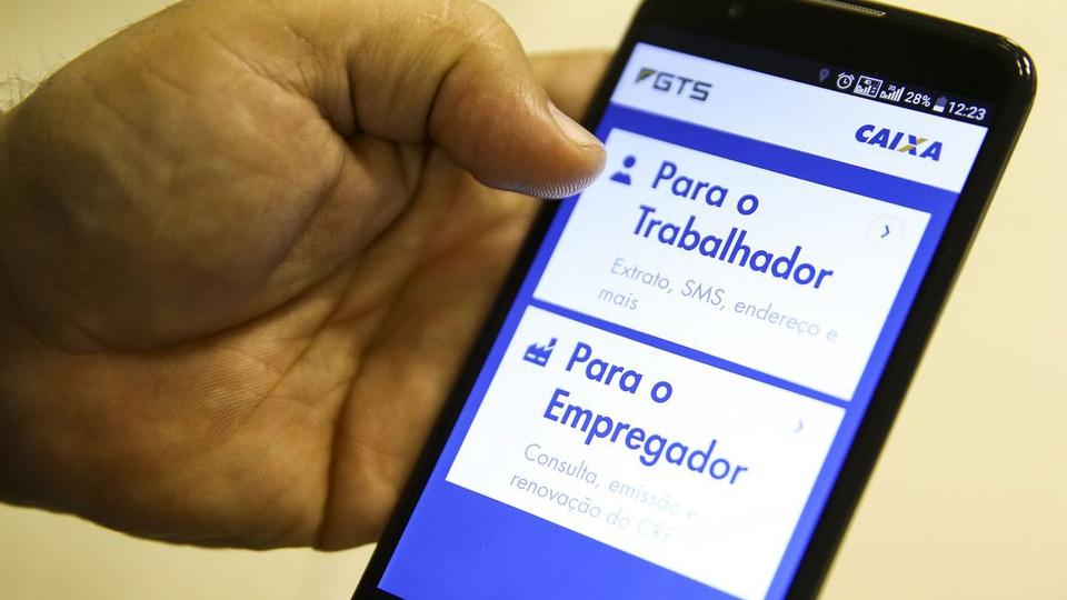 Golpe do FGTS em 2021: enquadramento em mão segurando celular. Na tela, é possível ver página sobre FGTS