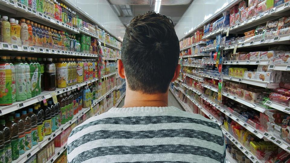 Cartões de compras em São Paulo: homem, de costas, em corredor de supermercado