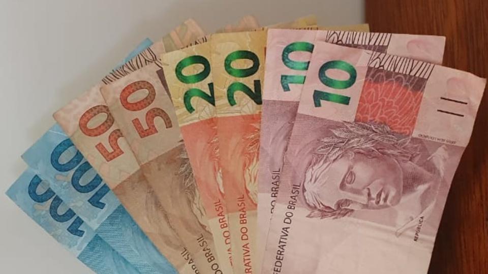 reformular auxílio emergencial junto com o Renda Brasil: leque de dinheiro com notas de cem, cinquenta, vinte e dez reais