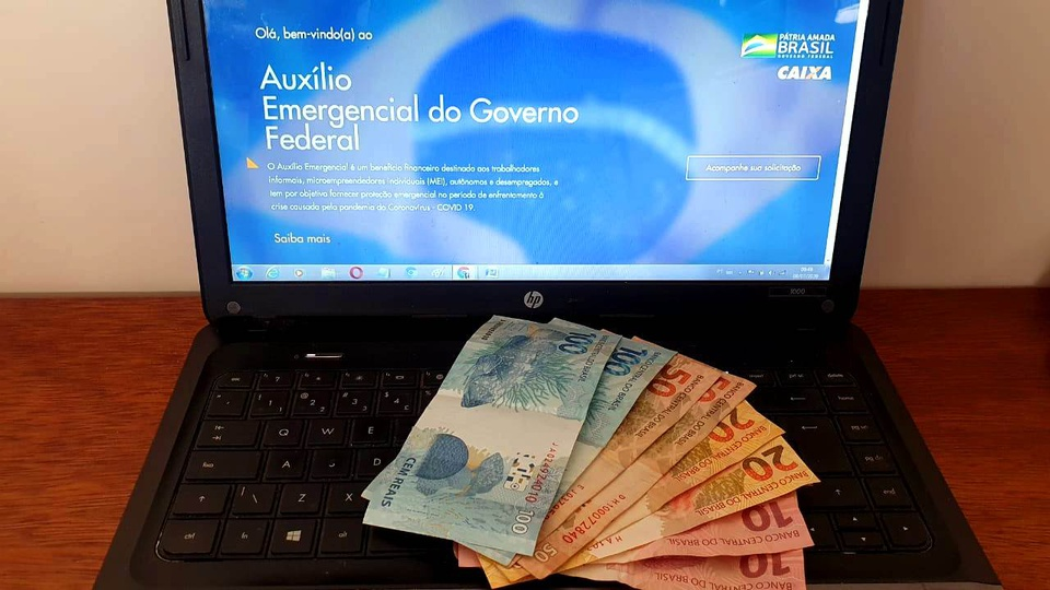 Auxílio emergencial: notas de 100, 50, 20 e 10 reais em cima do notebook aberto