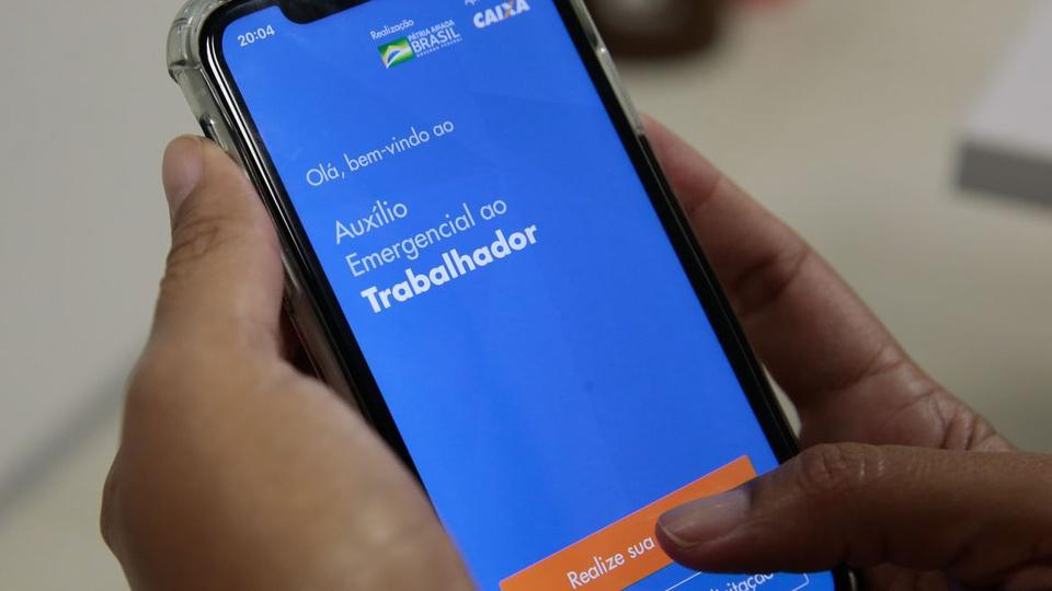 Prorrogação do auxílio emergencial em 2021: enquadramento em mão mexendo em celular. Na tela do aparelho, é possível ver a página do auxílio emergencial