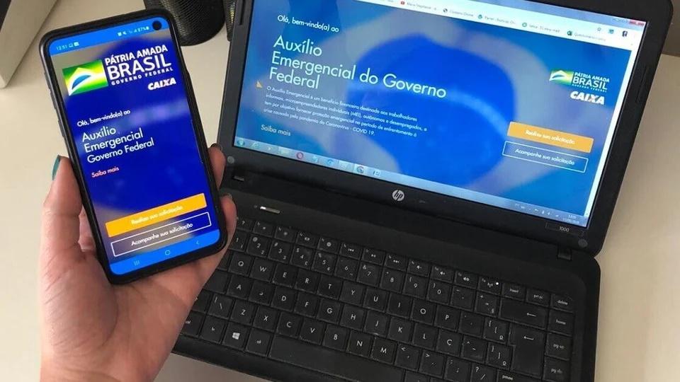 Cadastro para auxílio emergencial 2021: mão segurando celular. Na tela do aparelho, é possível ver a página do programa auxílio emergencial. No plano de fundo, tem um notebook com a mesma página aberta