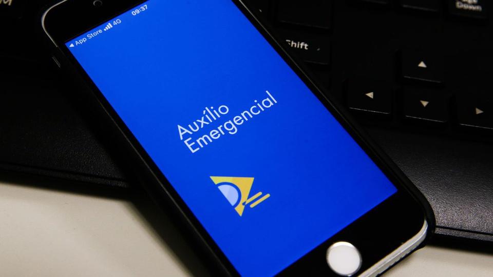 Auxílio emergencial para quem foi negado em 2020: celular disposto em mesa. Na tela, é possível ver a página do auxílio emergencial