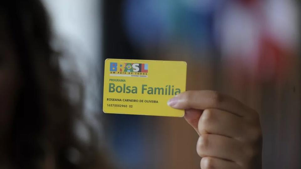 Revisão cadastral e bloqueio do Bolsa Família: mão segurando cartão do Bolsa Família
