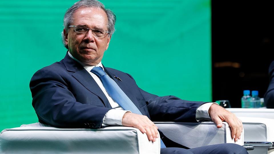 Guedes afirma que ministros do STF têm salários baixos: imagem de Paulo Guedes vestindo terno e gravata sentado em cadeira