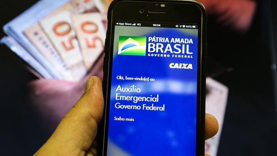 auxílio emergencial: a imagem mostra mão segurando celular aberto no app do auxílio emergencial e notas de dinheiro desfocadas atrás