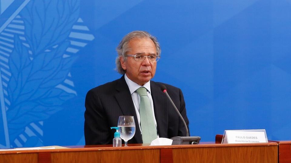 reforma tributária: Paulo Guedes sentado numa mesa onde há um microfone e um copo de água